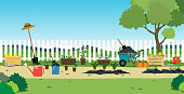 Garden plants and agricultural equipment with white fence.