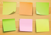 Vector collection of post it notes in several colors on the wooden plate for your own text or image.