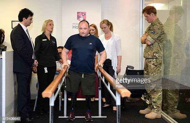 Prince Harry watches as Lt Alistair Spearing a Royal Engineers Officer who was badly wounded losing both legs above the knees whilst on deployment in...
