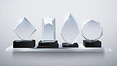 Realistic glass trophy awards, transparent diamond winner prizes on shelf vector illustration. Collection of award and trophy transparent glass