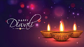 Realistic, Illuminated Oil Lamps on shiny bokeh background for Indian Festival of Diwali celebration.