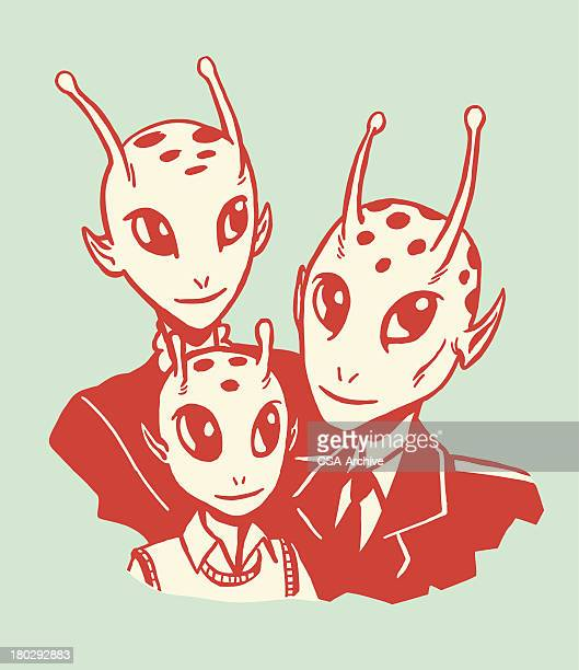 Red cartoon drawing of an alien family on green background