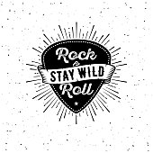 Rock and Roll sign. Stay wild. Slogan graphic for t shirt. Poster with plectrum, ribbon, starburst.