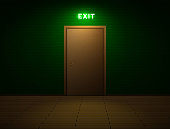 Dark room with shining exit sign above the door. All font licenses are checked.
