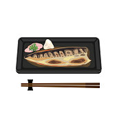 A plate of grilled saba fish with chopstick.