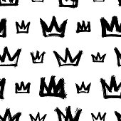 Seamless pattern with hand-drawn crowns isolated on white background. Rough brush painted shapes vector backdrop. Ink doodle style abstract grunge texture.