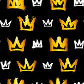 Seamless pattern with white and gold hand-drawn crowns isolated on black background. Rough brush painted shapes. Ink street-style abstract grunge illustration.