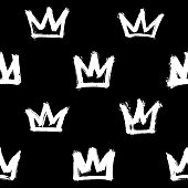 Seamless pattern with white hand-drawn crowns isolated on black background. Rough brush painted shapes vector backdrop. Doodle style abstract grunge texture.