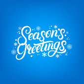Seasons Greetings hand written lettering with falling snow and snowflakes. Christmas inspirational calligraphy quote. Blue background. Vector illustration.