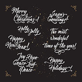 Set of Christmas and New Year related holiday brush lettering on black background. Great for greeting cards and holiday design.