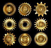 set of vintage, patterned brass and gold gears on a black background