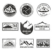 Set of nine mountain travel emblems with grunge texture. Camping outdoor adventure vector emblems, badges and  patches. Mountain tourism, hiking. Forest camp labels in vintage style