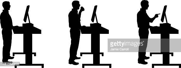 Silhouette of man standing at stand up desk