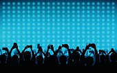 silhouette of people raise hand up in concert with smart phone and digital dot pattern on blue color background