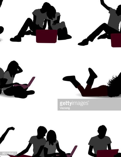 Silhouette of young couple using laptop