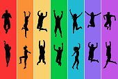 Silhouettes of men and women jumping on rainbow background