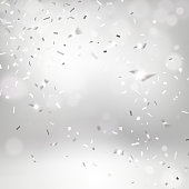 silvery falling confetti on a light background