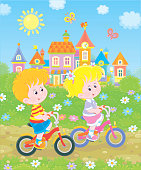 Little kids riding bicycles near a cute small town with colorful houses among green trees on a sunny summer day, vector illustration in a cartoon style