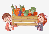 Smiling boy and girl with a wooden crate full of fresh vegetables
