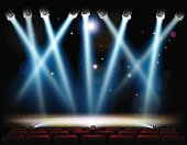 A theater or theatre stage and with footlights and spotlights and red audience seats in rows