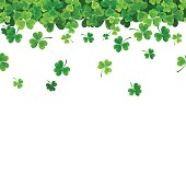Vector St. Patrick's day horizontal seamless background with green falling shamrock on white.