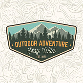 Stay wild, outdoor adventure patch. Vector illustration. Concept for shirt or print, stamp or tee. Vintage typography design with mountains and forest silhouette. Outdoor adventure badge.
