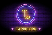 The Capricorn zodiac symbol, horoscope sign in trendy neon style on a wall. Capricorn astrology sign with light effects for web or print.