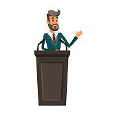The lecturer stands behind the rostrum. The speaker lectures and gestures. A young politician speaks to the public. Orator broadcasts on the podium.