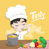 The young chef is tasting his delicious soup and happy in working time.