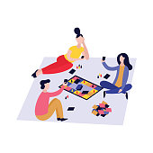 Three friends playing board game together, young people having fun during table top card competition on the floor. Isolated cartoon characters in flat style, vector illustration on white background.