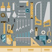 Set of tools hanging on peg board wall with shelf and drawers