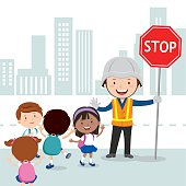Traffic guard helping kids crossing road by holding a stop sign.