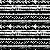 Tribal art ethnic borders monochrome seamless pattern. Aztec vintage repeating background texture in black and white, circles, stripes, lines, zigzag, embroidery. Chalk hand drawn on black board imita