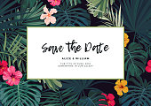 Tropical wedding invitation design with hibiscus flowers and exotic palm leaves on dark background. Vector illustration.