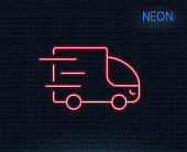 Neon light. Truck delivery line icon. Express service sign. Transportation symbol. Glowing graphic design. Brick wall. Vector