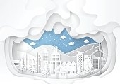 Urban cityscape on snow winter background.Paper art style of nature and environment conservation concept design.Vector illustration.