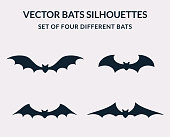 Vector bats silhouettes isolated on white background. Set of four bats with different shapes. Icons for Halloween design.