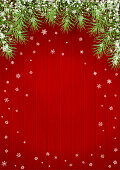 Christmas background with fir branches on red wooden background