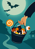Vector flat illustration of person's hand carrying a trick-or-treat bucket full of Halloween candy, on a background of night landscape with trees and house in a distance, full moon, flying bats.