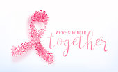 Vector illustration of breast cancer awareness background. Big pink bow consist on little tapes isolated on light backdrop. We are stronger together lettering text sign