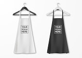 Vector white and black cotton kitchen apron set with clothes hangers closeup isolated on white background. Design template, mock up for branding, advertising etc. Cooking or baker concept.