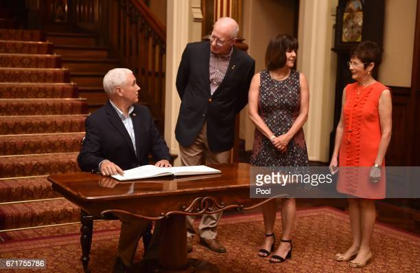 S Vice President Mike Pence signs the visitors book at Government House with the Governor of New South Wales David Hurley and their wives Karen and...