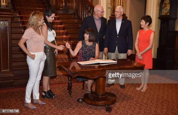 S Vice President Mike Pence watches his wife Karen sign the visitors book at Government House with his daughters Charlotte and Audrey and the...