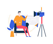 Video blogger - colorful flat design style illustration on white background. Unusual composition with a creative man streaming online in front of the camera, sitting on a chair, talking