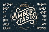 Vintage decorative font named 'Amber Taste' with label design and background pattern