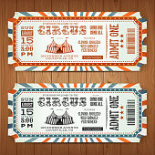 Illustration of two circus tickets, with big top, admit one coupon mention, bar code and text elements for arts festival events, on wood tiles background