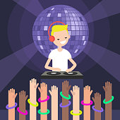 A DJ wearing headphones and scratching a record on the turntable / Party people. Disco night. Raised hands wearing neon bracelets on the dance floor. Young people having fun at the night club.