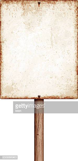 Weathered blank placard with wooden post isolated on white