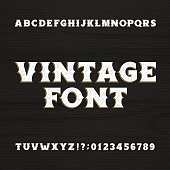 Vintage typeface. Retro distressed alphabet font on a wooden background. Wild west bold letters and numbers. Rough vector typeset for labels, headlines, posters etc.