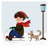Winter Christmas collection. A boy is riding a sled and playing with a dog